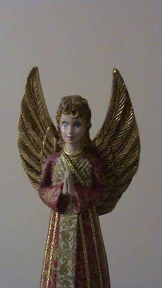 Deixe sua decoração de Natal mais bonita! <br>Peça em gesso representando um anjo com as mãos postas. Asas folheadas na cor ouro (folha de ouro); vestido em decoupage com guardanapos e detalhes do vestido em fita dourada. A peça é forrada com papel camurça, evitando danificar superfícies. <br> <br> ÚLTIMA PEÇA