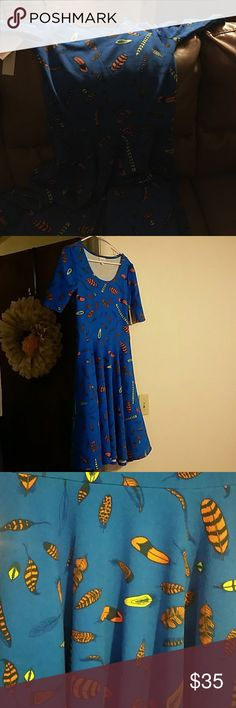 Lularoe Nicole dress size small The Nicole dress come right below the knee, has pockets, and is 3/4 length sleeve. The second picture is not the Nicole I have, just a pic so you can see what it looks like on.  Mine is a size small & is a very sought after feather print. LuLaRoe Dresses Midi