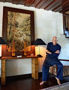 Armani sits on a vintage armchair in the entrance hall, next to a framed Chinese tapestry. The lamps are vintage Armani/Casa, and the walls are clad in Saint-Maximin limestone.
