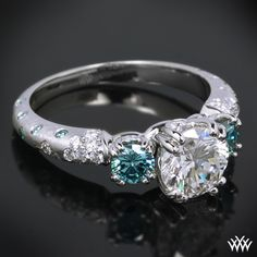 """3 Stone """"Petite Champagne"""" Diamond Engagement Ring has been customized and holds 2 Blue Diamond Side Stones and sprinkled Blue Diamond Melee. A 1.25ct A CUT ABOVE ® Hearts and Arrows Diamond completes the whole look."""