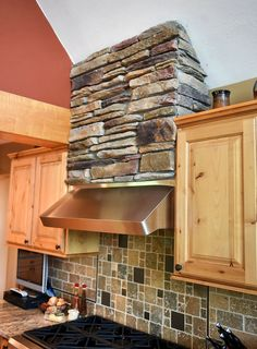 Stone detailing over stove top hood in kitchen with travertine tile backsplash and granite counters.