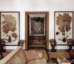 lovely eclectic living room with lots of wood and rusty rose colored accents. old rugs, large botanical art, old european feelings