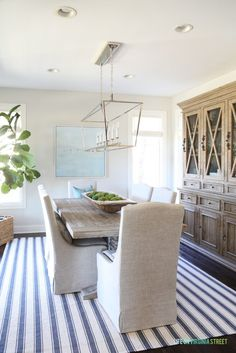 Coastal dining room with navy blue striped rug, beach artwork, fiddle leaf fig tree, dough bowl and reclaimed wood dining table.
