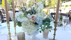 Blush roses are the focal flower of these lucious centerpieces. Nestled in vintage milk glass vessels which seem to disappear, allowing the beautiful neutral colors to take the stage. Set alongside vintage brass candlesticks, taupe candles and taupe and blush tealite candle holders. Event styling, floral and decor by On The Side Events & Service.