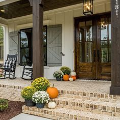 Darling front porch fall decor display. Love the pops of color with the pumpkin and mums on this sweet farmhouse style porch. Brick pavers, wood french doors, complimentary shutters and perfect little outdoor pendant. click for more information.  #fall #exterior #sconce #outdoordecor #autumn #pumpkins #lighting #interiordesign #rustic #rusticglam #fall #falldecor #falltones #frontporchfalldecor #fallporchfalldecor #frontporchfalldecorfarmhouse #frontporchfalldecorideas