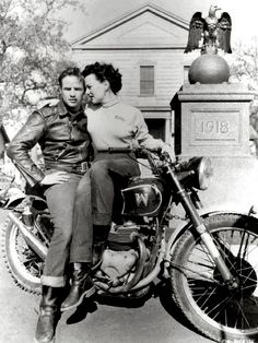 """Marlon Brando and Yvonne Doughty astride a British Matchless twin cylinder motorcycle– its 'M' logo badge is actually upside-down to resemble a 'W', which makes sense since it belonged to stunt rider """"Wally"""" Allbright."""