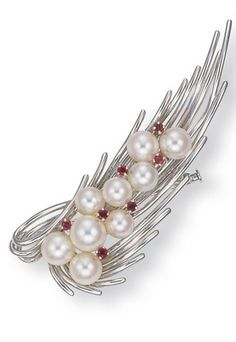 A CULTURED PEARL AND 14K WHITE GOLD, OBI CLASP/BROOCH, BY MIKIMOTO The wirework stylised foliate motif, enhanced by cultured pearls and circular-cut rubies, 7.4 cm wide With jeweller's mark for Mikimoto.