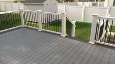 Gray composite decking w/ a double Walnut feature board, white composite rail w/ black round aluminum balusters
