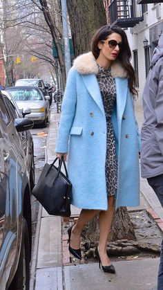 Amal Clooney wearing a blue coat and black tote bag