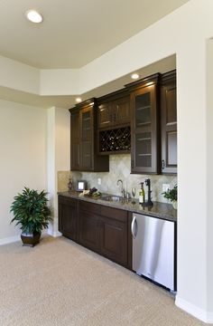 Wet bar with dark cherry stain cabinetry, tile backsplash and stone countertop
