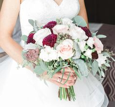 Blush and burgundy bridal bouquet with roses, dahlias, and seeded eucalyptus.
