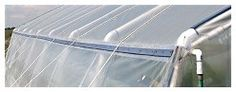 PVC greenhouse makes use of wooden lath on purlins and outside rafters to hold the poly in place.