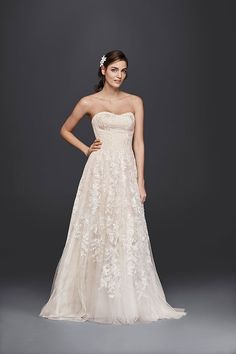 Hand beading and a blush underlayer give Melissa Sweet's A-line lace wedding dress its warm glow. Exclusively at David's Bridal.