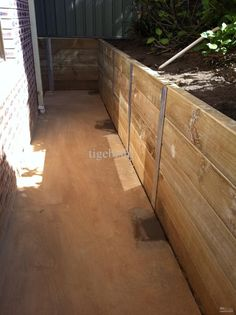 Walkway to side of building with timber retaining wall