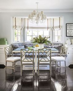 Family room booth - Sunlight streams through Roman shades in the breakfast area. The banquette wears Perennials' Bazaar fabric from David Sutherland. Below an existing chandelier, Dayna chairs from Ballard Designs gather around the custom Parsons-style dining table.