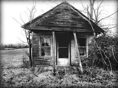 The best part about this picture is the curtains still left in the windows.  Someone hung those curtains up with care at some point.  Someone picked the fabric out especially for the windows in the front of this old, tiny, little house.