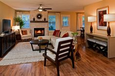 20 Beautiful Living Room Layout with Two Focal Points   Living Room with neutral tones, dark wood, texture, and pops of orange.