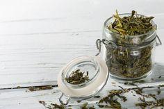 green tea leaves sencha in jar on wooden background