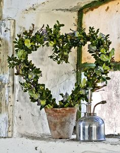 Instant Topiary To make this sweet arrangement, bend a wire hanger or floral wire into the shape of a heart. Place the ends into a pot filled with floral foam. Attach bundles of boxwood and hydrangea flowers with wire to the frame.