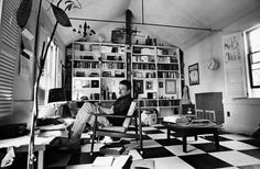 This is Kurt Vonnegut, my favorite author, is his own study. I want something like this for myself, especially the massive shelf, framed pictures and prints, and a round coffee table.
