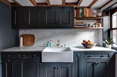 Ainda na cozinha, se destacam os armários com acabamento cinza escuro (quase preto). Na parte molhada da bancada há uma cuba de semi-encaixe