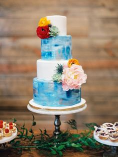 Blue watercolor wedding cake with colorful floral accents: http://www.stylemepretty.com/2015/11/23/oak-knoll-ranch-spring-wedding/ | Photography: Charla Storey - http://www.charlastorey.com/