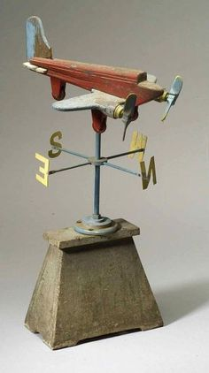 Folk Art  Airplane weather vane  Painted wood and metal  Red two-prop plane with blue wings raised on blue metal support with yellow directional letters on gray plinth, ht. 31 1/2 in. (80.0 cm)