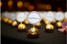 A single chocolate with a place name attached by cocktail stick. This one uses Ferrero Rocher but any wrapped truffle or chocolate would of course work equally well.  Combine a little favour with the place cards, saving money and very efficient!
