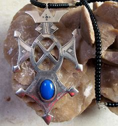 Tuareg Amulet with Blue Agath stone, signed by the Silversmith at the back in Tifinagh language. €68    Total Length Onyx Beads and Silvermelange beads: 44 cm     Pendant with Blue Agath gemstone: 9 cm x 5 cm     Beautiful Piece!  www.Tuareg-Jewelry.com  https://www.facebook.com/TuaregJewelry
