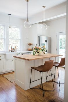 white kitchen with wood floors and wood countertop on the island, with white walls and cabinets, lots of natural light, and simple decor