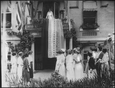 Alice Paul unfurling the ratification banner over the railing of the National Woman's Party headquarters on August 26, 1920 -- the day the 19th Amendment was ratified. The banner was one of the most important to the NWP. For every state that ratified suffrage, the members sewed on a star. When Tennessee ratified the amendment, the final star was sewn on. [Courtesy of the National Woman's Party]