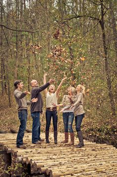 The Ramseyers throwing leaves in the air while standing on a log bridge.
