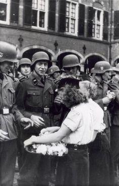 Vertrekkende van het Vrijwilligers  Legioen om dienst te nemen bij de Waffen SS krijgen op het Binnenhof in Den Haag bloemen aangeboden van meisjes van de Nationale Jeugdstorm.1941