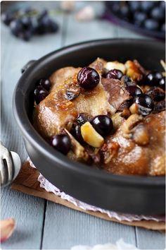 Cuisses de canard confite à l'ail et au raisin - 4 cuisses de canard confites, 1 grappe de raisins noirs Muscat, 6 gousses d'ail (roses de Lautrec), 125 g de champignons de Paris, Poivre