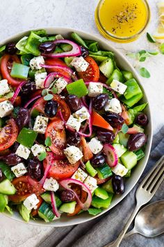 Top shot looking down on a bowl of greek salad with a jar of homemade dressing
