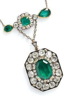 An Antique Emerald and Diamond Pendant. Centring an emerald-cut emerald weighing approx. 3.50 cts., framed by old mine-cut diamonds, and suspended from a bar set with emerald- and pear-shape emeralds and old mine-cut diamonds, silver-topped gold mount, and suspended from trace link chain.