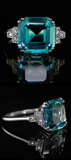A 1930's Art Deco original. The fine and rare blue zircon measuring approximately 10.4mm x 10.1mm and estimated to weigh 6.00cts. Mounted with three old brilliant cut diamonds set to each shoulder. A lovely original Art Deco ring.
