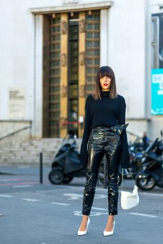 Evangelie Smyrniotaki in a black top, black patent leather pants and white pumps and purse.