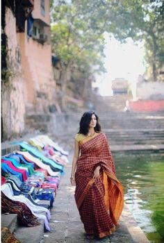 A typical indian girl walking alongside temple pond in a saree Photo; malavika mohanan..