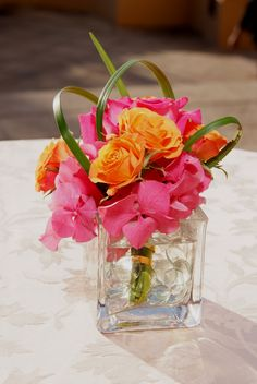 Love the bear grass loops over the flowers.  Orange Rose and Pink Rhododendron Centerpiece