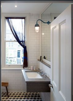 The walls of this bathroom are lined in subway tiles while the floor uses a modified chevron tile pattern.
