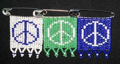 """Zulu love letter Peace Signs ribbons are in three color combinations of mini glass beads representing air (white), earth (green) and sky (blue). They measure approximately 1"""" x 1.5"""". Each piece is handmade on a safety pin so the love letter can be worn."""