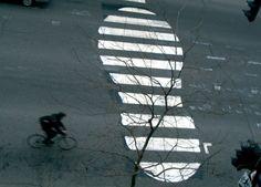 """Strisce pedonali a forma di orme o proiettili, forbici  che tagliano le strade, zip che chiudono la segnaletica orizzontale. Una protesta davvero insolita contro la dipendenza dal petrolio e la cultura dell'auto. È quella a cui ha dato vita il canadese Peter Gibson, a.k.a. Roadsworth, uno street artist che, vernice spray e stencil alla mano, crea opere d'arte urbana di contestazione contro la cultura """"oil-friendly"""", seguendo il desiderio di avere più piste ciclabili in città"""