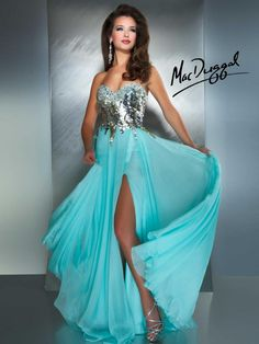 Strapless prom gown features a sweetheart neckline and fully embellished bodice. Flowy skirt with a sexy high slit. This glamorous dress is perfect for prom or pageant.