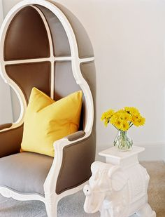 Round Chair - A white elephant side table beside an upholstered chair with a yellow pillow