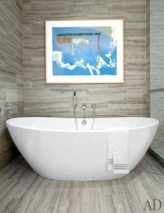 A work on paper by Helen Frankenthaler in the travertine-clad master bath | archdigest.com