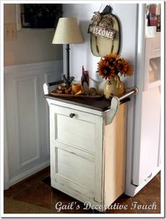 Build a wooden trash can holder to hide the trash. Build it so that the top can be used for decor! Paint it with a distressed finish.