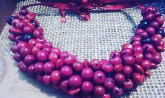 Maxi colar feito com sementes de açaí em tons de vinho e pau Brasil na cor vermelha e feltro.