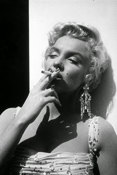 Portrait of American actor Marilyn Monroe - in a white beaded gown leaning against a wall smoking a cigarette, while on the Century Fox studios set of director Walter Lang's film, 'There's No Business Like Show Business'. Marilyn Monroe Smoking, Fotos Marilyn Monroe, Joe Dimaggio, Viejo Hollywood, Old Hollywood, Rare Photos, Vintage Photos, Rare Images, Marilyn Monroe Cuadros