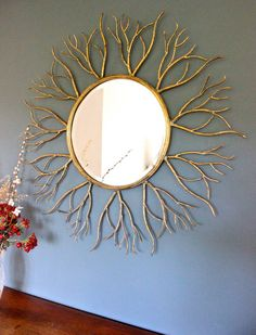 Large Golden Twig Mirror This is a gorgeous substantial mirror with a vintage glamour feel to it. This mirror is a focal point in any room with its aged gold metal sunburst made from gold twigs radiating from a round glass mirror.
